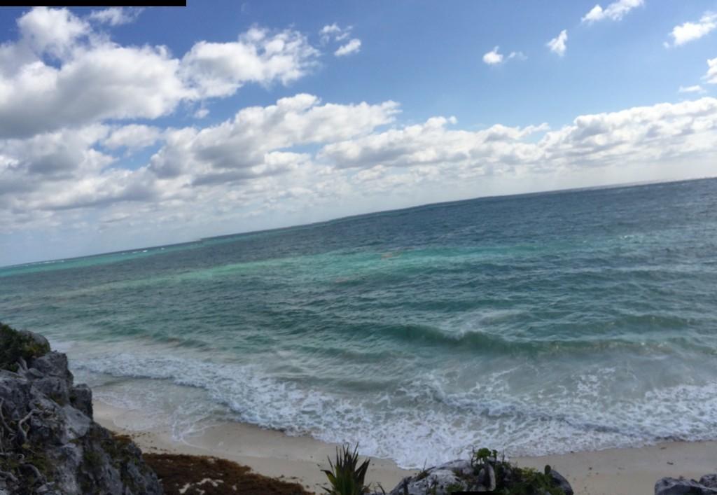 praia de tulum, ao fundo, a linha preta bem em cima do mar é um recife de corais
