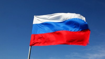 stock-footage-big-russian-tricolor-flag-flutters-in-wind-against-blue-sky