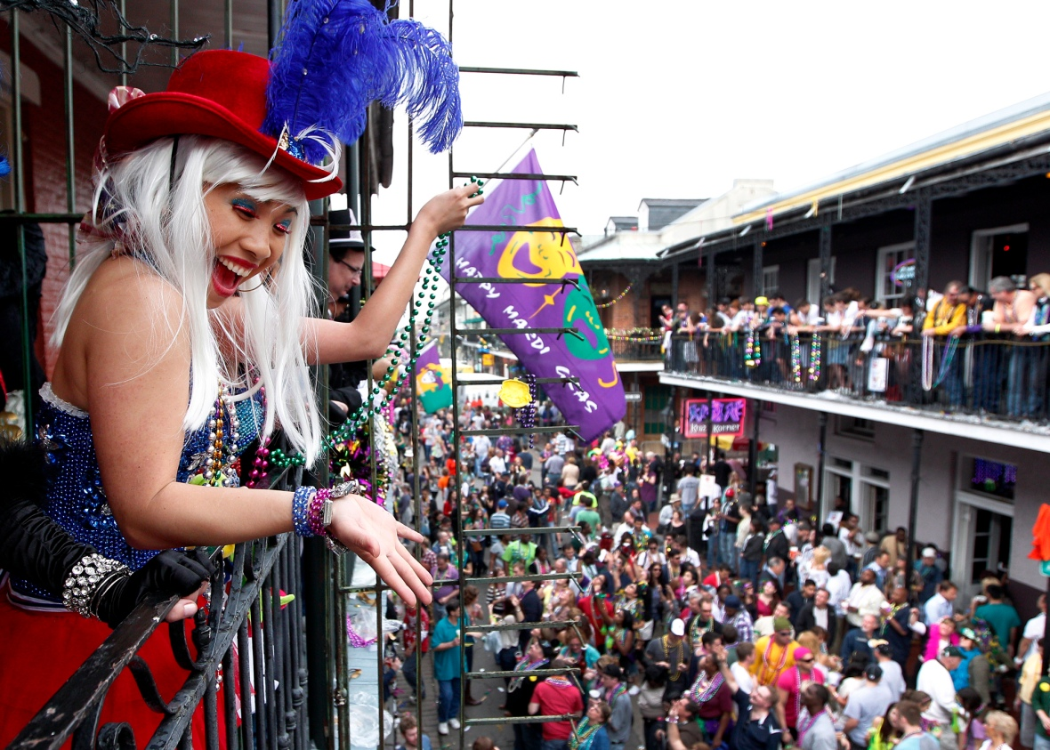 Malia Miyashiro, of California, throws beads from a Bourbon St. balcony to Mardi Gras revelers in French Quarter in New Orleans, Friday, Feb. 17, 2012. (AP Photo/Jonathan Bachman)