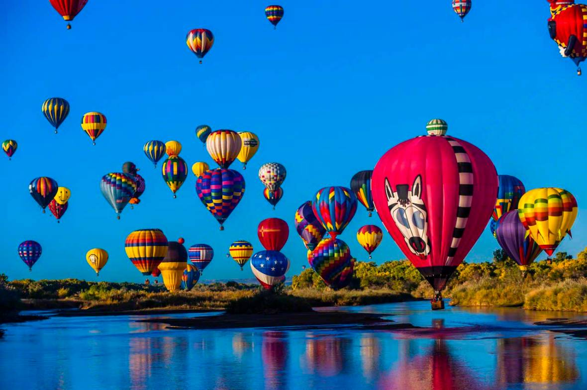 Hot air balloons flying low over the Rio Grande River just after sunrise,
