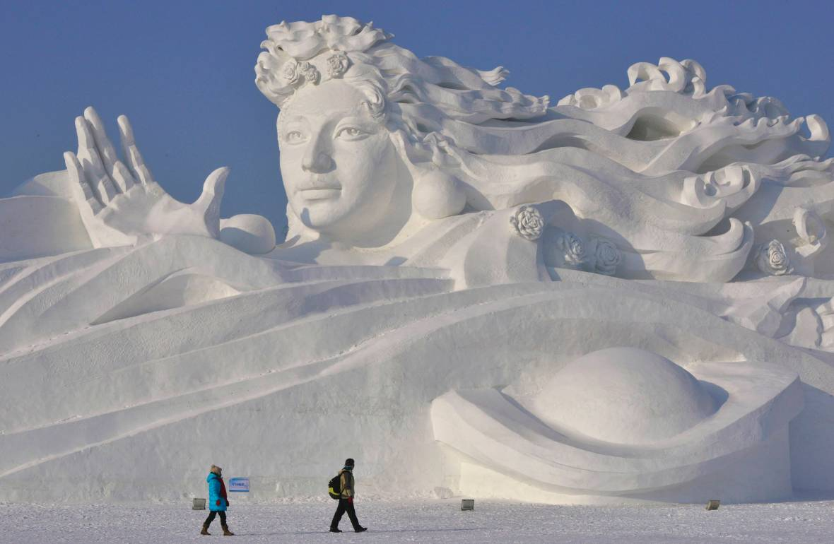 Visitors walk past a giant snow sculpture ahead of the 30th Harbin Ice and Snow Festival in Harbin